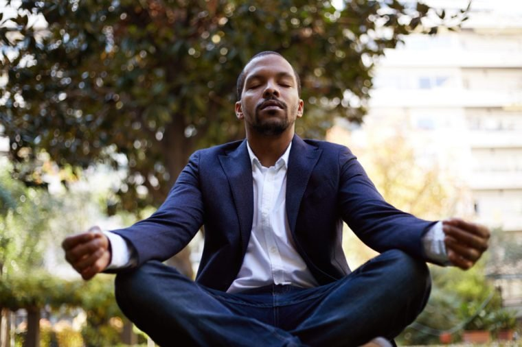 Young american african businessman in informal clothes meditating in lotus pose taking a deep breath outside corporate office.Business yoga and stress free environment.Peace of mind concept.Blurred