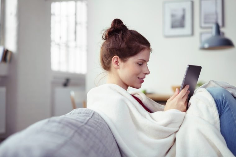 Happy young woman enjoying an e-book on her tablet computer as she relaxes with her feet up on the couch wrapped in a warm blanket, side view with copyspace