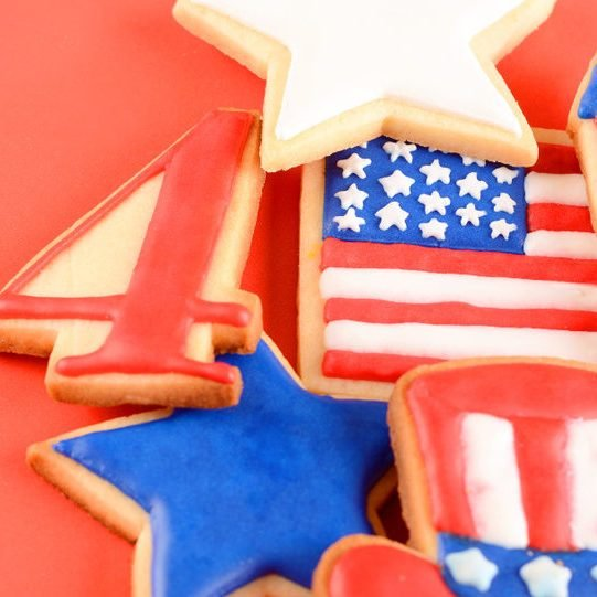 Patriotic cookies for 4th of July on red background. Independence day concept