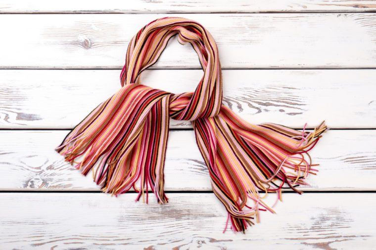 Multicolored striped scarf, wooden background. Colorful knitted scarf for women.