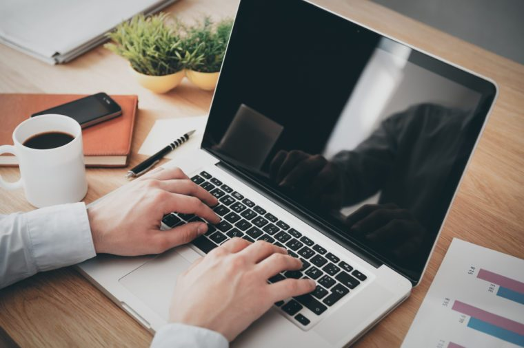 Businessman at work. Close-up top view of man working on laptop while sitting at the wooden desk