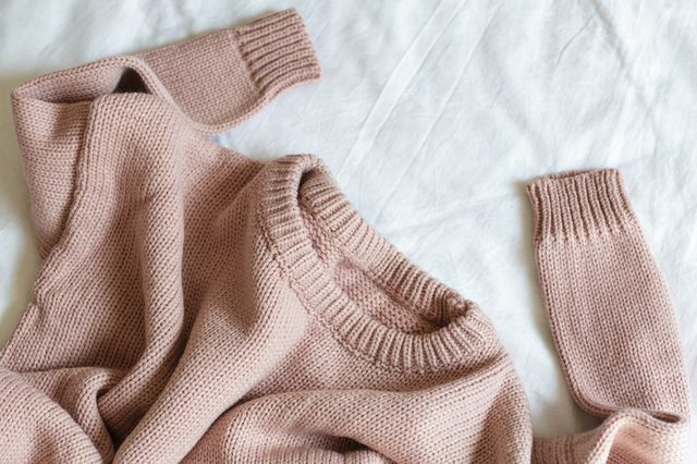 pink knitted sweater lies on a white blanket