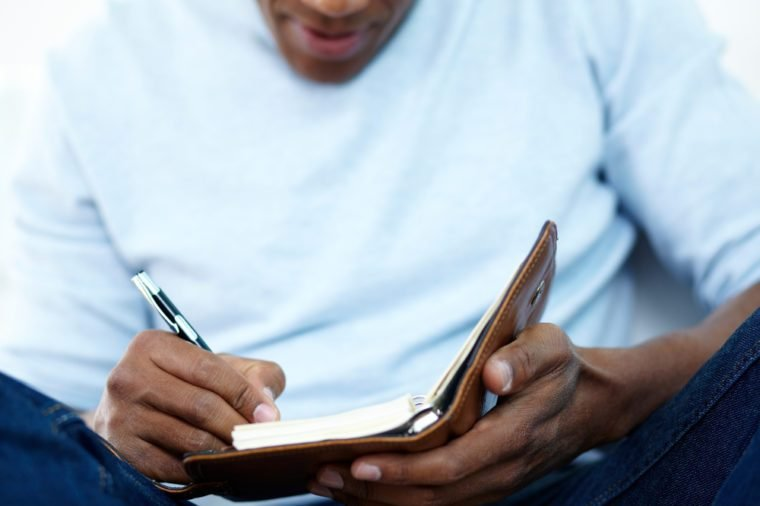 Close-up of young African man writing something in notepad