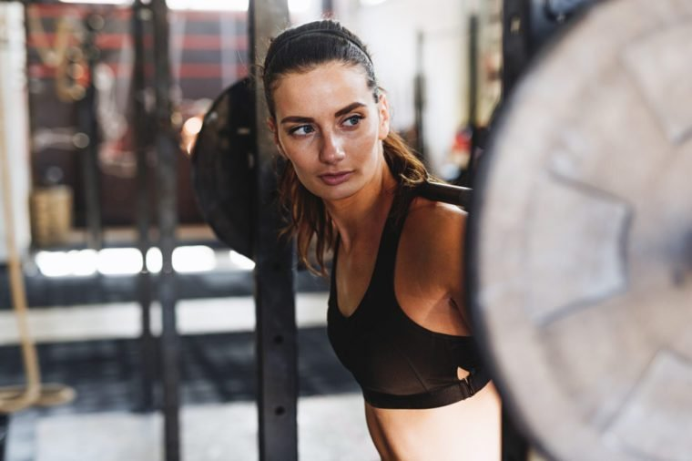 Young sporty woman prepairing barbell for training