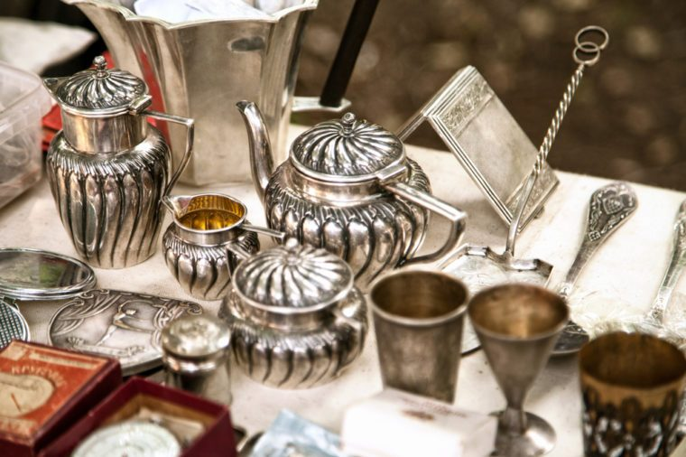 Antique silver teapots, creamer and other utensils at a flea market. Old metal tableware collectibles at a garage sale