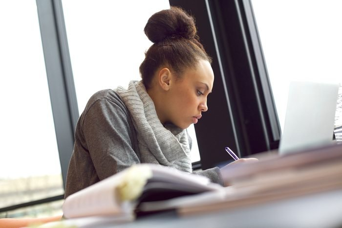 Young african american woman taking notes from books for her study. Sitting at table with books and laptop for finding information.