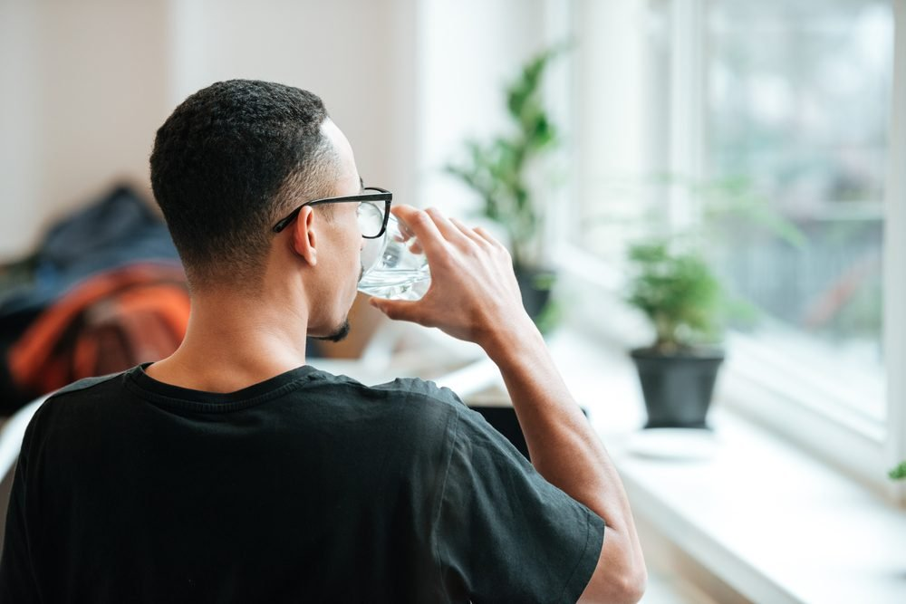 Back view of a young african man drinking water out of glass during coffee break at cafe