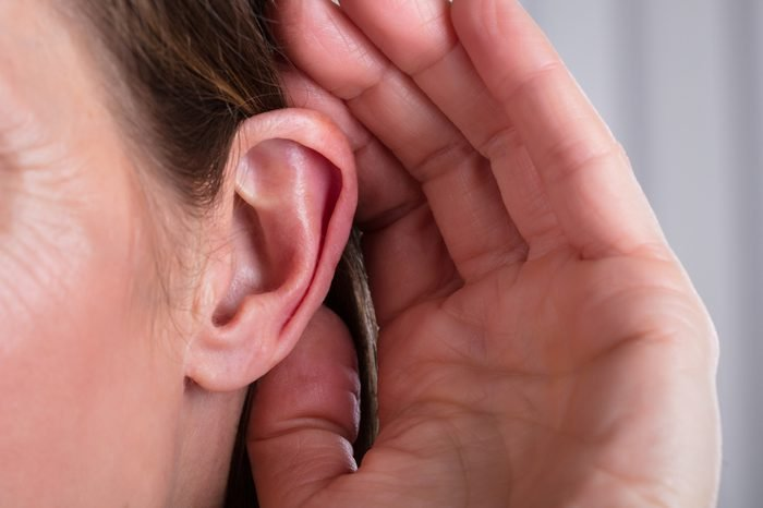 Woman Listening With Her Hand On An Ear
