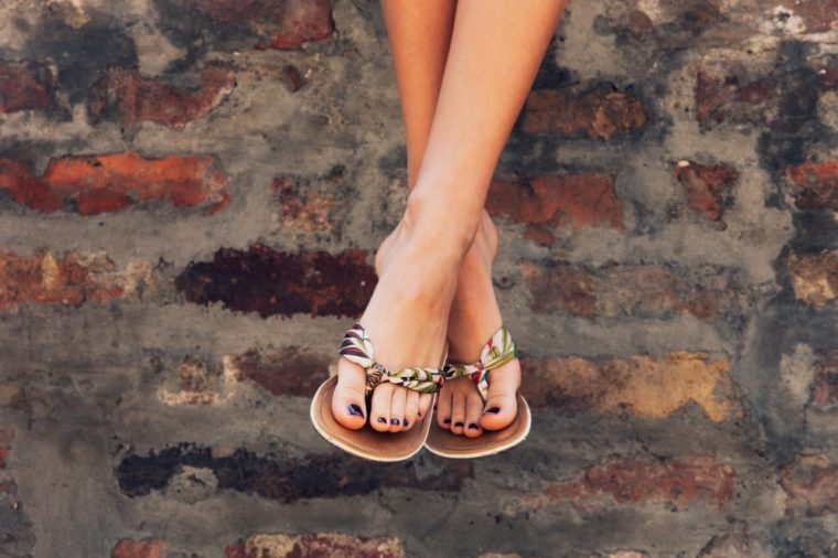 woman legs in summer flat slippers outdoor day shot in city