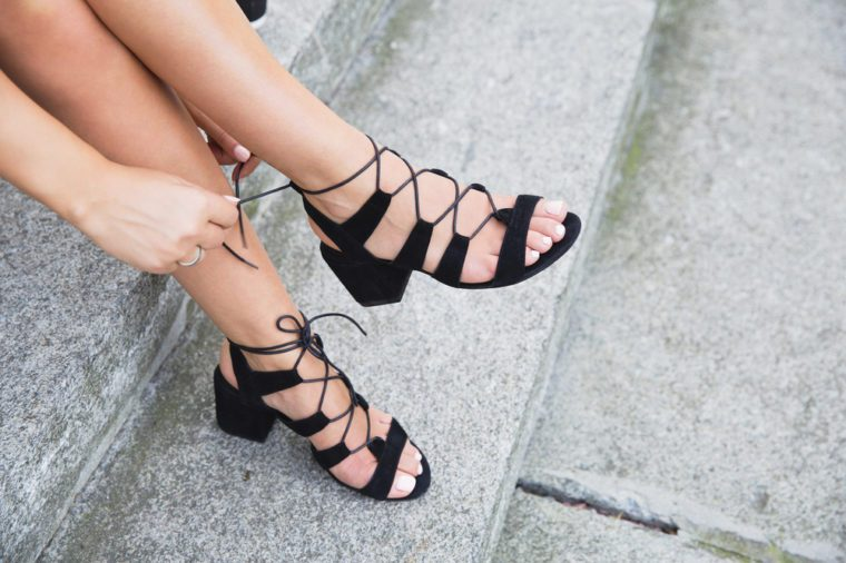 Tanned young woman's legs in black suede leather sandals on the stairs. Stylish summer outfit, street fashion look