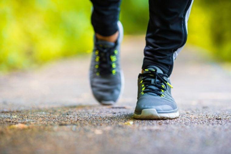 Close-up on shoe of athlete runner man feet running on road