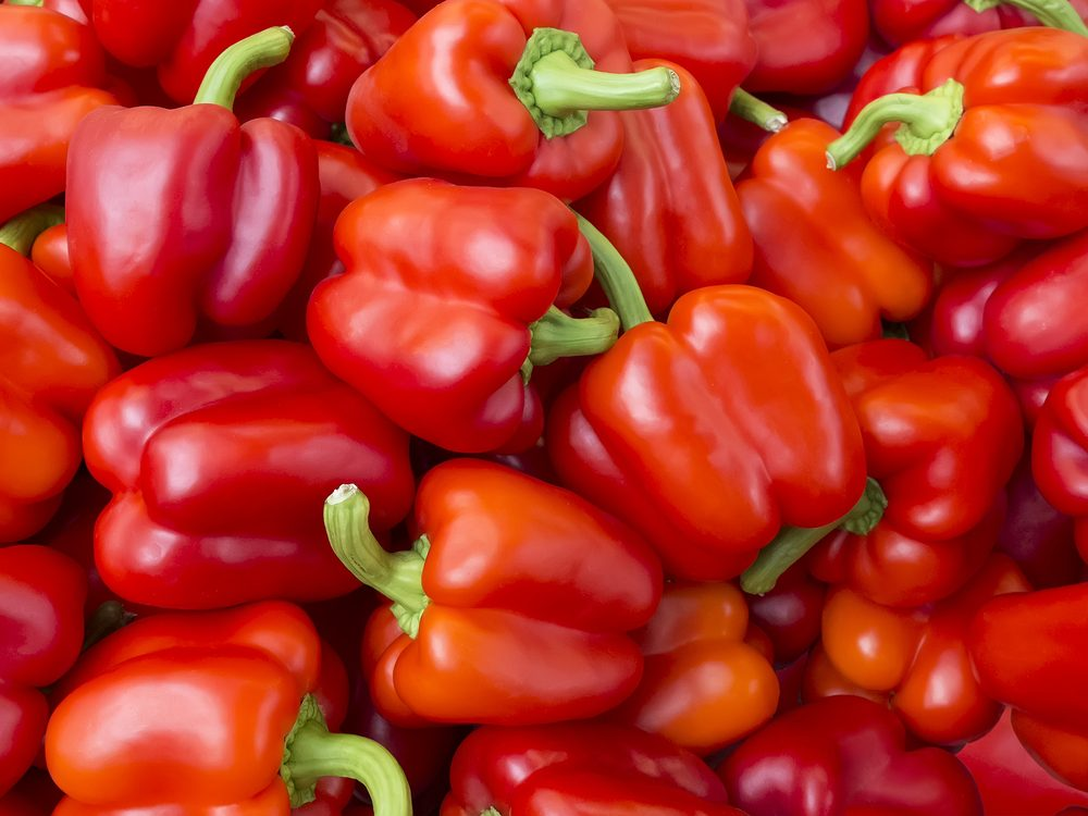 A lot of red bell peppers. Vegetables background. Top view.