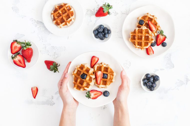 Belgian waffles with fresh strawberry and blueberry on white background. Flat lay, top view