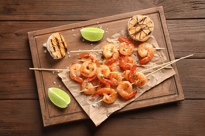 Board with delicious fried shrimp skewers, lime and garlic on wooden background, top view