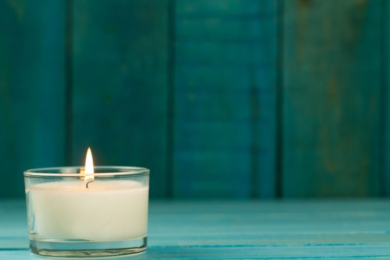 light burning brightly candles on old wooden background. Spa, meditation, ritual, flavored. turquoise color