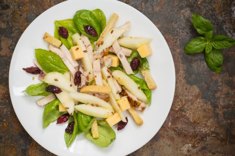 Chicken salad, pears, dried gooseberries and currants, cheese on basil leaves. Wooden background. Top view. Close-up