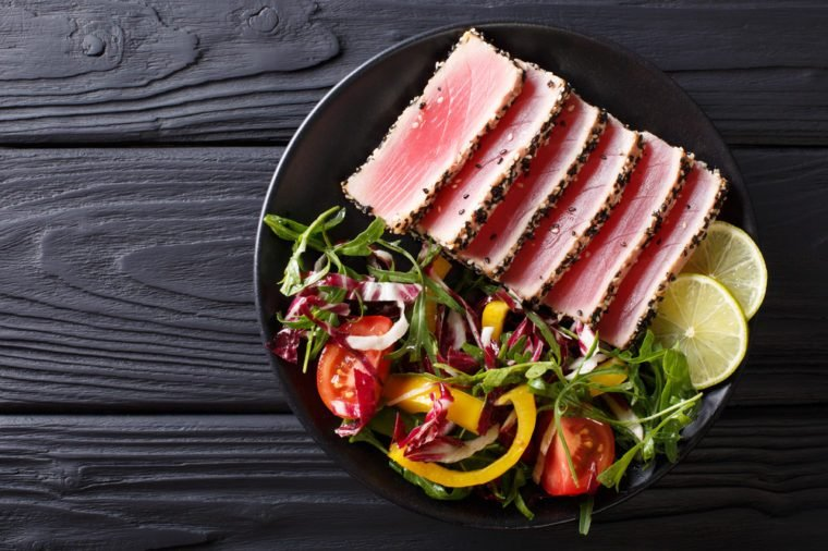 Close up of rare seared Ahi tuna slices with fresh vegetable salad on a plate. Top view from above horizontal