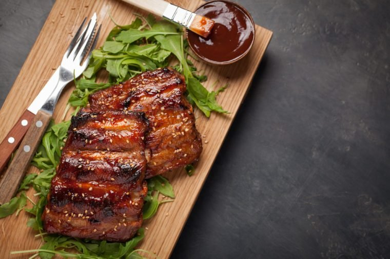 Closeup of pork ribs grilled with BBQ sauce and caramelized in honey on a bed of arugula. Tasty snack to beer on a wooden Board for filing on dark concrete background. Top view with copy space.