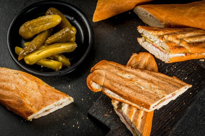 Cuban traditional food, snack, party food. Cuban sandwich from baguette with ham, pork, cheese, pickles. On black table copy space