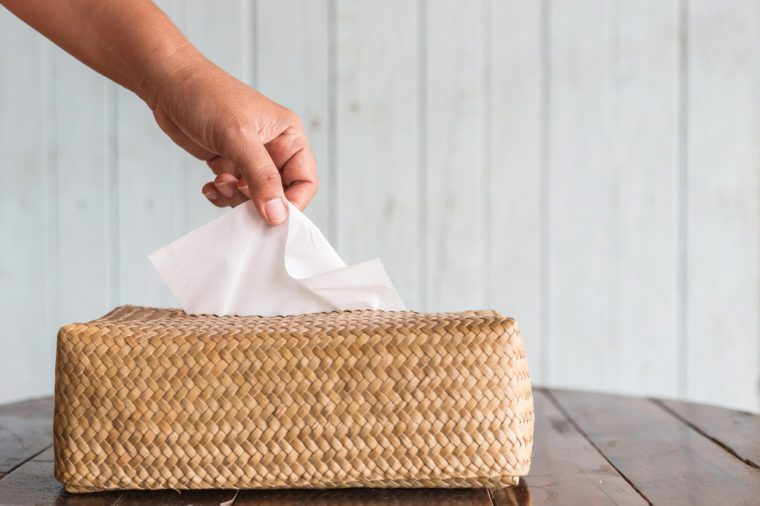 Hand picking white piece tissue paper from brown box