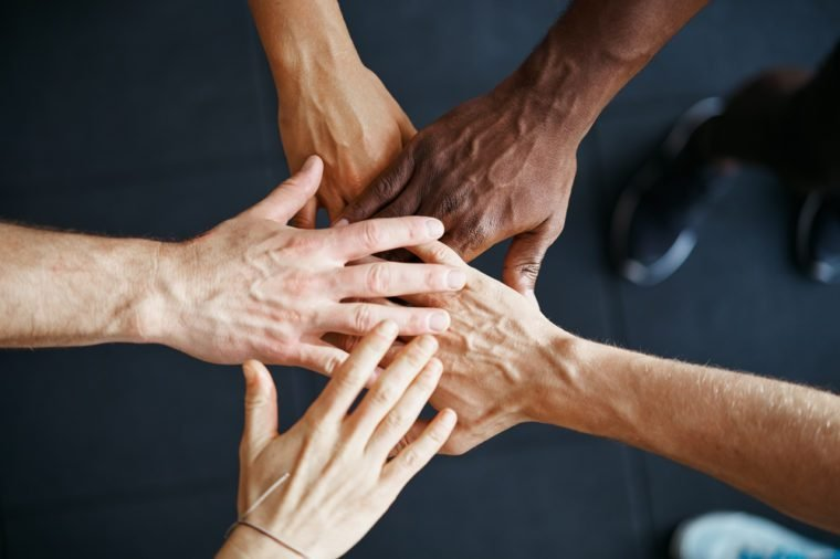 Closeup of a diverse group of people standing in a huddle with their hands together in a gym