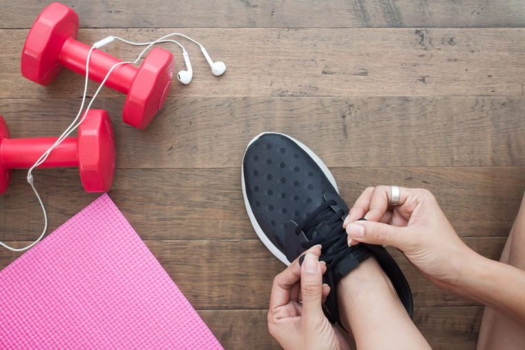 Overhead view of woman hands tying shoes with sport equipments on wood background
