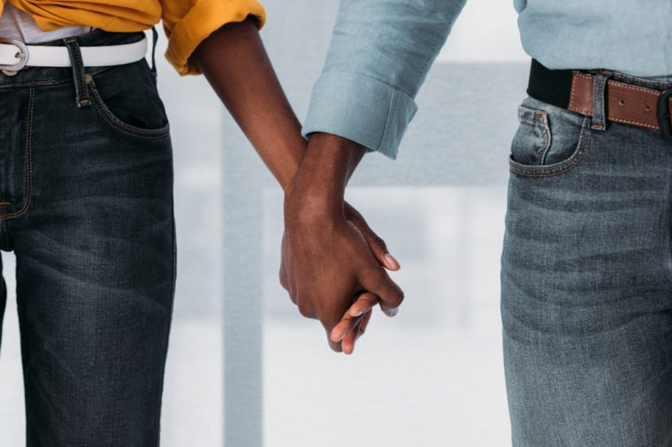 cropped image of african american couple holding hands at home