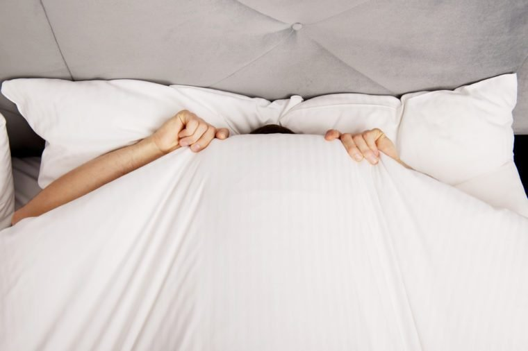 Funny man hiding in bed under the sheets.