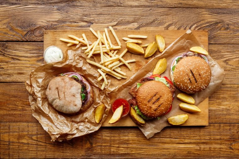 Fast food dish top view. Meat burger, potato chips and wedges. Take away composition. French fries, hamburger, mayonnaise and ketchup sauces on wood. Menu or receipt background