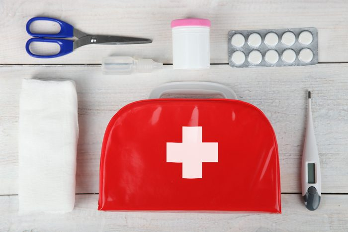 First-aid kit and medication on a wooden background.