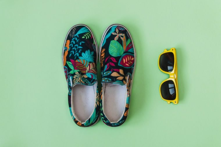 Flat lay fashion set: colored slippers shoes with palm and flowers print and yellow sunglasses on pastel background. Top view.