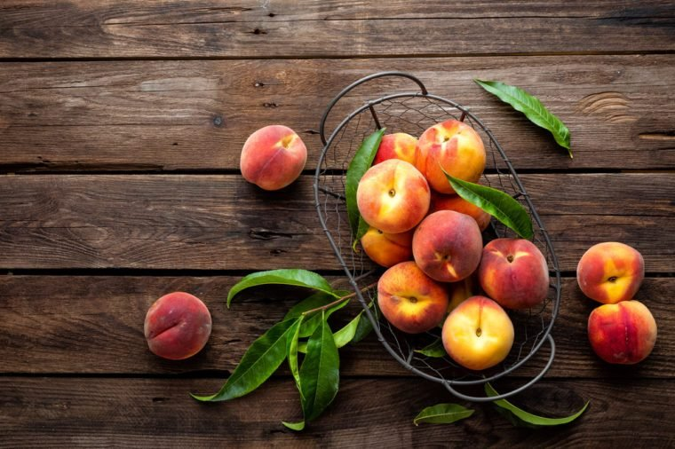 Fresh peaches fruits with leaves in basket on dark wooden rustic background, top view
