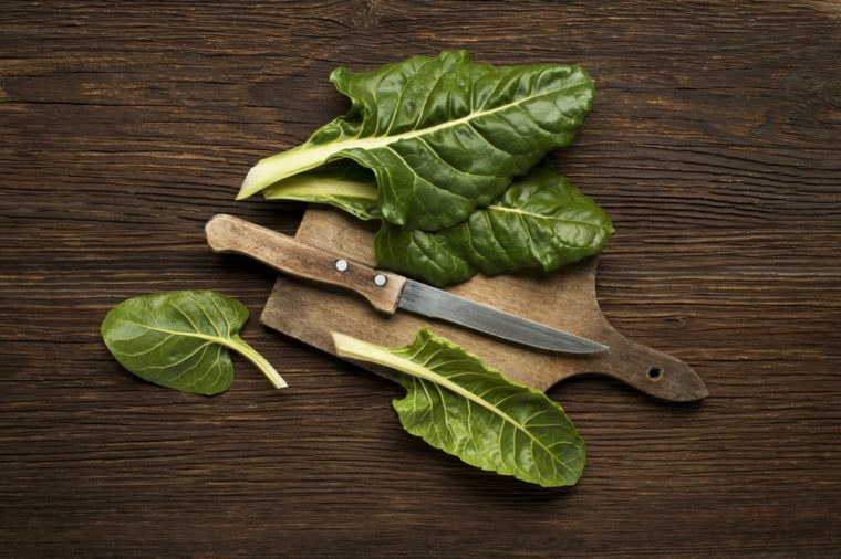 Fresh swiss chard leaves on a wooden background.