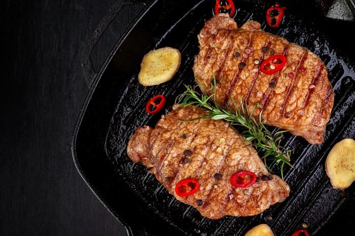 Grilled pork steak in grill pan with rosemary, pepper chilli and ginger on wooden board. Top view. Copy space.