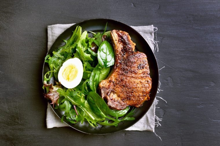 Grilled pork steak with green salad in plate on dark background, top view