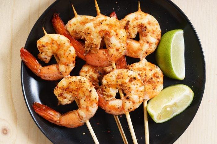 Grilled shrimps on skewer with lime slices and salad