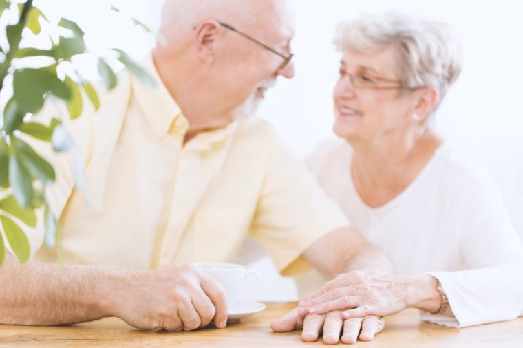 Happy, blurred elder couple sitting at a table and holding hands