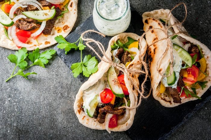 Healthy snack, lunch. Traditional Greek wrapped sandwich gyros - tortillas, bread pita with a filling of vegetables, beef meat and sauce tzatziki. On black stone table Copy space