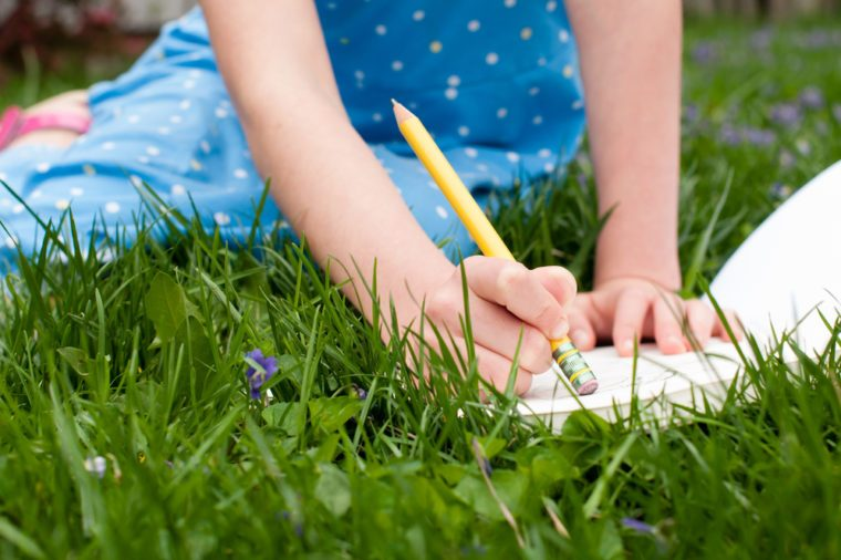 A little girl holds a pencil as she erases a mistake on a pad of drawing paper. She is wearing a blue dress and is sitting in a grassy yard.