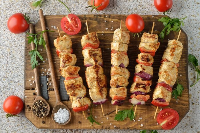 Kebabs with turkey fillet on a brown background