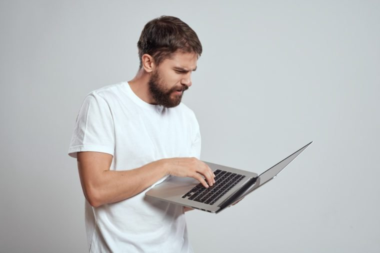 serious man with a beard working behind a laptop on a gray background
