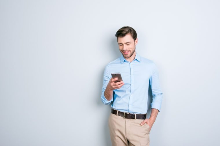 Portrait with copy space of attractive, cute man holding smart phone in one hand and another one in pocket, checking email through wifi, 3G internet over grey background