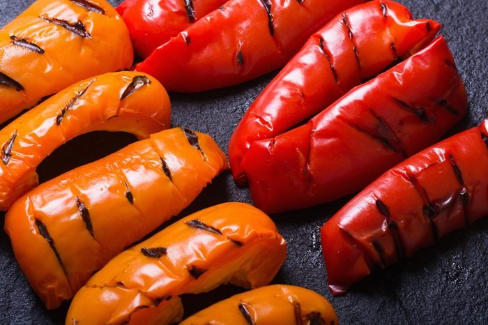 Orange and red grilled peppers on black stone .