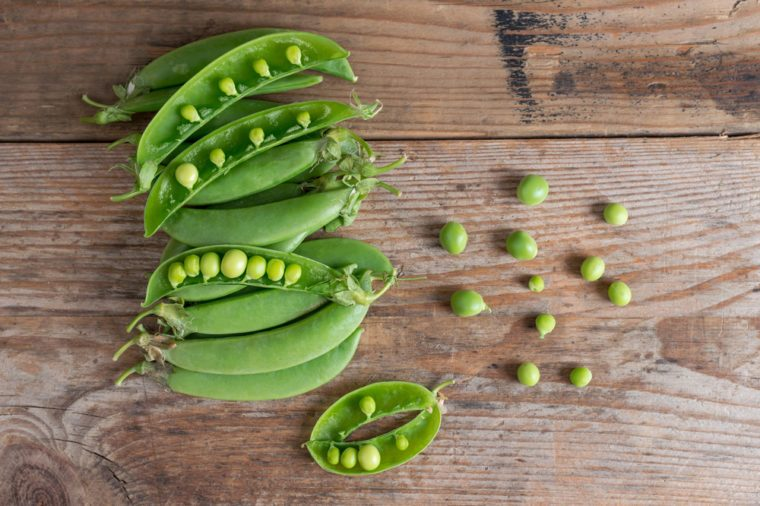 Pile of Sugar snap peas on the wooden background. Top view.