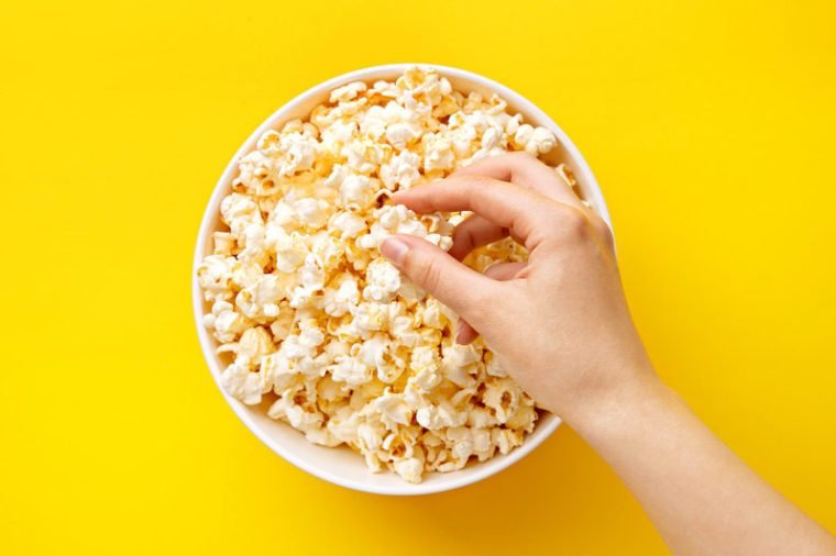 Popcorn viewed from above on yellow background. Woman eating popcorn. Human hand. Top view