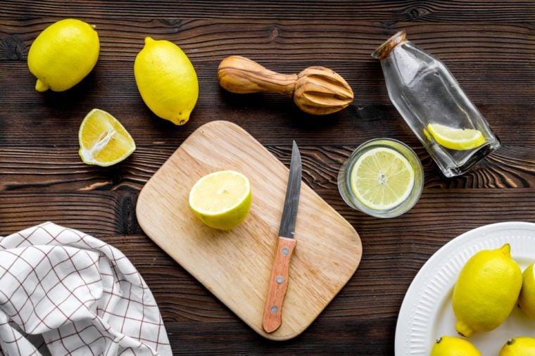 Prepare refreshing beverage lemonade. Lemons, juicer, bottle, knife, cutting board on dark wooden background top view