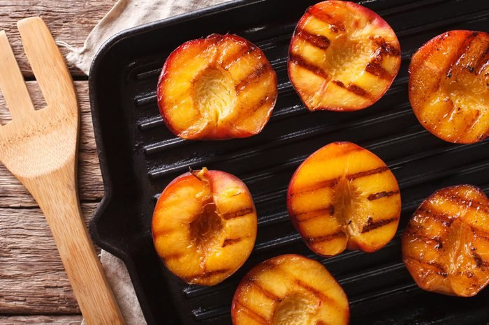 Ripe peaches on a a grill pan on a table close-up. Horizontal view from above