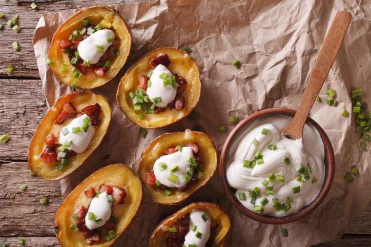 Rustic potato skins with cheese, bacon and sour cream close-up on the table. Horizontal view from above