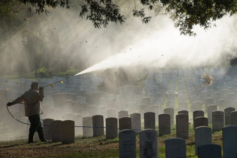 Groundskeepers power-wash headstones at Arlington National Cemetery in Arlington, Va