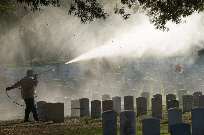 Groundskeepers power-wash headstones at Arlington National Cemetery in Arlington, Va